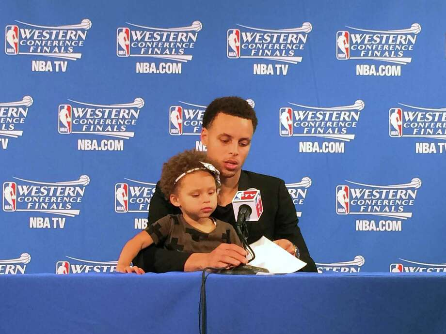 Golden State Warriors' Stephen Curry holds his daughter Riley during the post game press conference after the first game of their Western Conference finals of the NBA Playoffs in Oakland, California, on Tuesday, May 19, 2015. The Warriors defeated the Houston Rockets 110-106. Photo: Sarah Todd /Associated Press / Sarah Todd / SFBay.ca