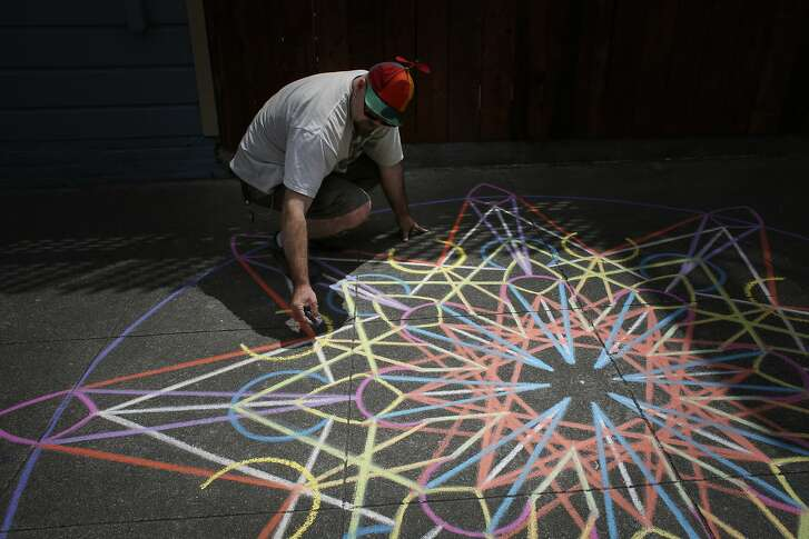 Chalk artist Nikolas Larson works on a geometric design near his home in the Mission on Friday May 18, 2015 in San Francisco, Calif.