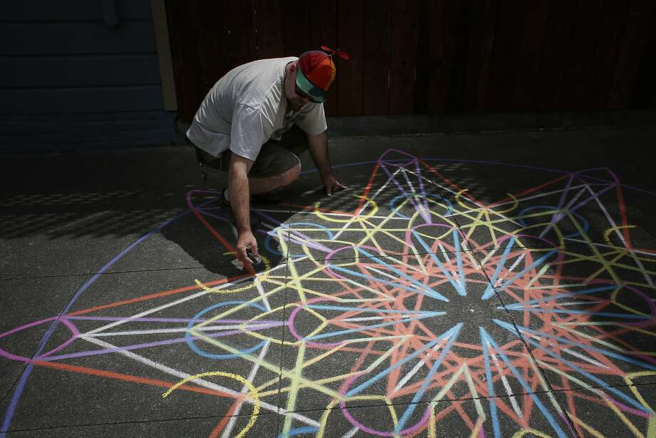 Chalk artist Nikolas Larson works on a geometric design near his home in the Mission on Friday May 18, 2015 in San Francisco, Calif. Photo: Mike Kepka, The Chronicle