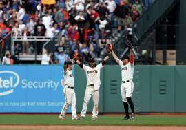 San Francisco Giants outfielders Nori Aoki, left, Angel Pagan, center, and Hunter Pence celebrate after defeating the Los Angeles Dodgers, Thursday, May 21, 2015, in San Francisco. The Giants defeated the Dodgers 4-0. (AP Photo/Beck Diefenbach)