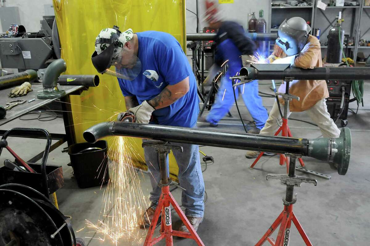From left: Julio Robles, Juan Reyes and Jorge Robles work in the shop fabricating pipes at Comfort Systems USA at 9745 Bent Oak Drive Tuesday May 12, 2015.(Dave Rossman photo)