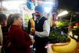"""Satwinder """"Bill"""" Multani (right), owner, speaks with Dina Hilliard (left), Safe Passage executive director and neighborhood resident talk next to a new display of fresh fruits and vegetables for sale at Daldas neighborhood market during it's grand re-opening on Thursday, May 21, 2015 in San Francisco, Calif."""