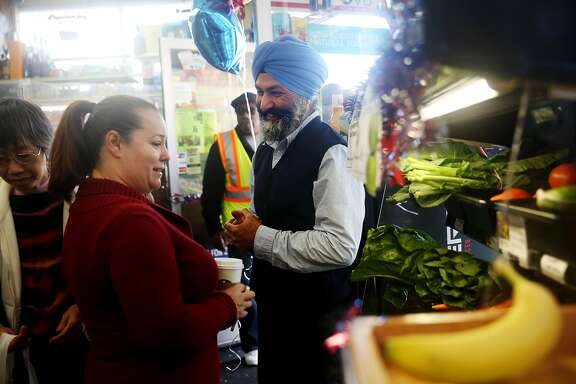 "Satwinder ""Bill"" Multani (right), owner, speaks with Dina Hilliard (left), Safe Passage executive director and neighborhood resident talk next to a new display of fresh fruits and vegetables for sale at Daldas neighborhood market during it's grand re-opening on Thursday, May 21, 2015 in San Francisco, Calif."