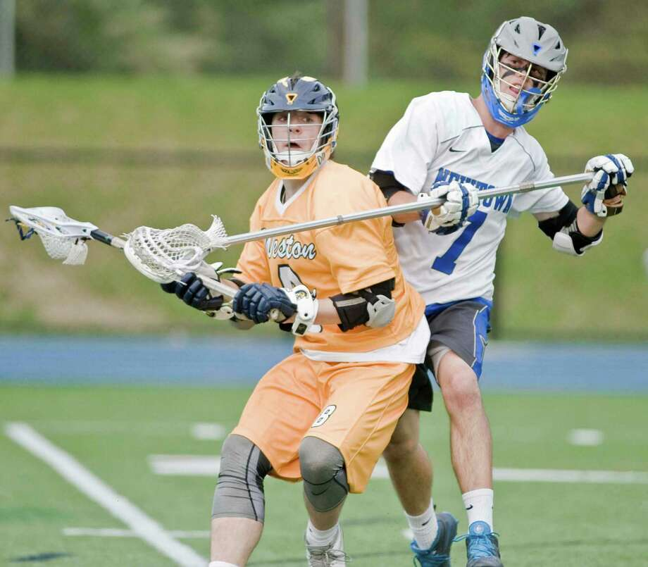 Weston High School's Austin Drimal is stick checked by Newtown High School's Cornelius Dunn during the SWC Division I quarterfinals, played at Newtown High School. Thursday, May 21, 2015 Photo: Scott Mullin / The News-Times Freelance