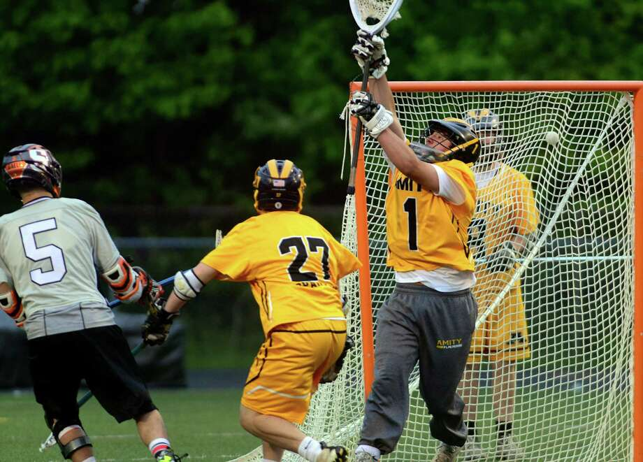 Shelton's Paul Russell, left, sends the ball past Amity goalie Matt Perrotti to score, during boys lacrosse action in Shelton, Conn. on Thursday May 21, 2015. Photo: Christian Abraham / Connecticut Post