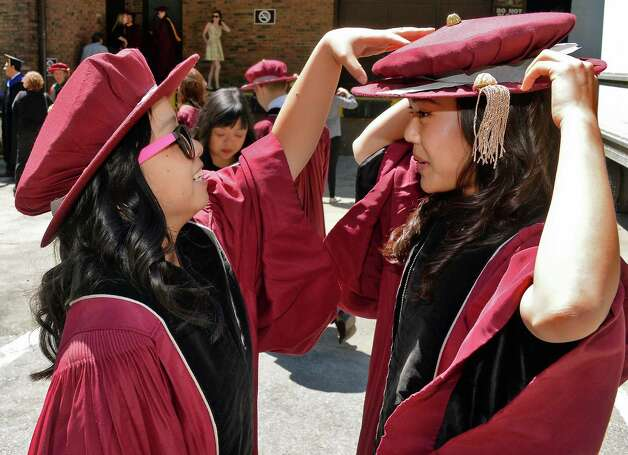 Elayna Ng, left, of San Francisco helps classmate Lisa Park of Anaheim with her cap before the start of Albany Medical College Commencement Thursday May 21, 2015 at SPAC in Saratoga Springs, NY.  (John Carl D'Annibale / Times Union) Photo: John Carl D'Annibale / 00031498A
