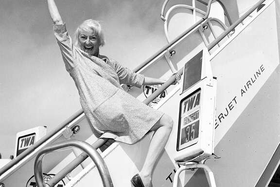 Phyllis Diller arrives in San Francisco on a TWA plane in 1964.