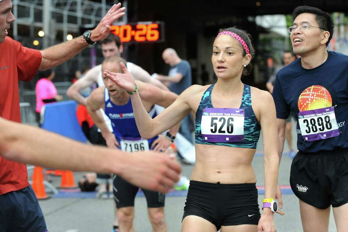 Karen Bertasso, center, of Scotia is the first woman to cross the finish line during the CDPHP Workforce Team Challenge on Thursday, May 21, 2015, in Albany, N.Y. More than 10,000 runners and walkers signed up from 500-plus organizations. (Cindy Schultz / Times Union)