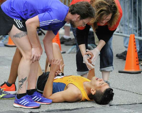 A runner receives medical attention when he collapses at the finish line during the CDPHP Workforce Team Challenge on Thursday, May 21, 2015, in Albany, N.Y. More than 10,000 runners and walkers signed up from 500-plus organizations. (Cindy Schultz / Times Union) Photo: Cindy Schultz / 00031895A
