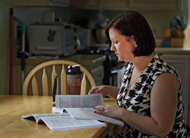 Kate Halligan, gets some reading done in her kitchen at her home Wednesday May 20, 2015 in Albany, N.Y.      (Skip Dickstein/Times Union) Photo: SKIP DICKSTEIN / 00031912A