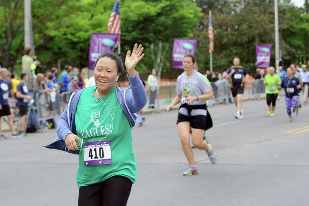 Amanda Cetinel of Green Tech High Charter School, center, waves to colleagues as she nears the finish line during the CDPHP Workforce Team Challenge on Thursday, May 21, 2015, in Albany, N.Y. More than 10,000 runners and walkers signed up from 500-plus organizations. (Cindy Schultz / Times Union) Photo: Cindy Schultz / 00031895A