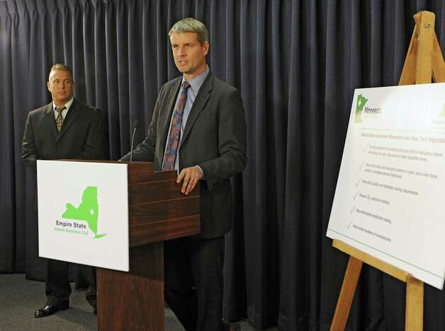 Dr. Kyle Kinglsey, founder and CEO of Empire State Health Solutions (ESHS) speaks at the Legislative Office Building as ESHS announces plans to produce cannabis-derived medications at a facility at the Tryon Technology Park and Incubator Center in Perth Thursday, May 21, 2015 in Albany, N.Y. Ralph Ottuso, chairman of the Fulton County Board of Supervisors, listens at left. (Lori Van Buren / Times Union) Photo: Lori Van Buren / 00031946A