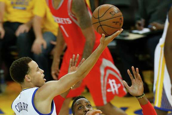 Golden State Warriors guard Stephen Curry (30) shoots a layup over Houston Rockets center Dwight Howard (12) and guard Jason Terry (31) during the third quarter of Game 2 of the NBA Western Conference Finals at Oracle Arena on Thursday, May 21, 2015, in Oakland. ( Karen Warren / Houston Chronicle )