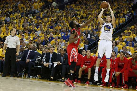 Golden State Warriors guard Klay Thompson (11) shoots a 3-pointer over Houston Rockets guard James Harden (13) during the third quarter of Game 2 of the NBA Western Conference Finals at Oracle Arena on Thursday, May 21, 2015, in Oakland.  ( James Nielsen / Houston Chronicle )