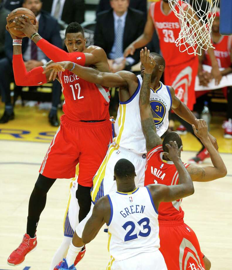 Dwight Howard, left, pulls one of his 17 rebounds away from the Warriors' Festus Ezeli during the first quarter Thursday night. Photo: Karen Warren, Staff / © 2015 Houston Chronicle