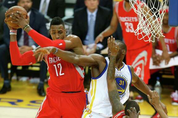 Dwight Howard, left, pulls one of his 17 rebounds away from the Warriors' Festus Ezeli during the first quarter Thursday night.