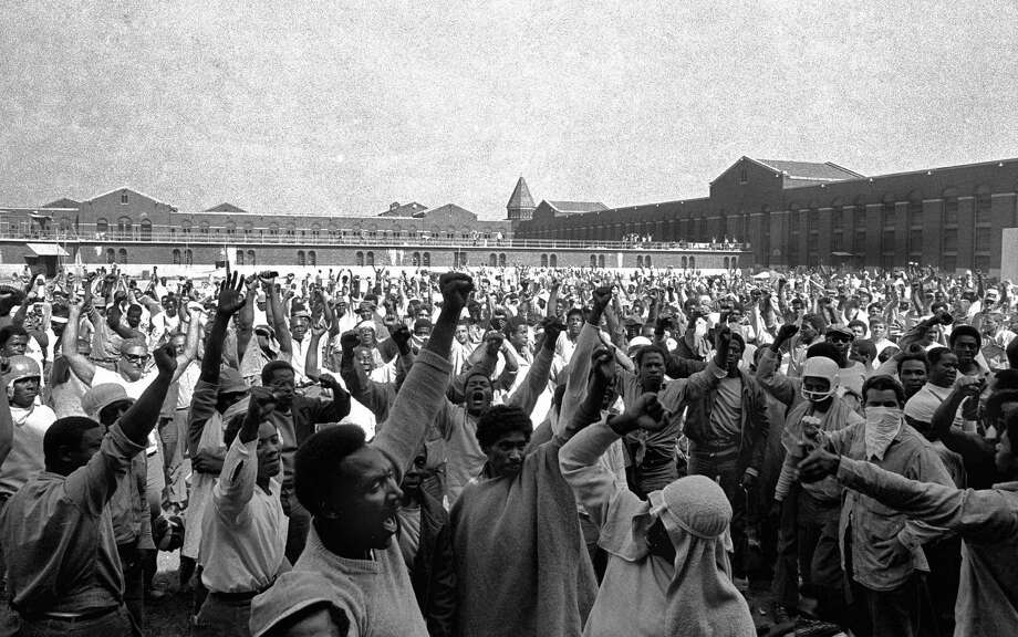 FILE - This Sept. 10, 1971 file photo shows inmates of Attica State Prison as they raise their hands in clenched fist salutes to voice their demands during a negotiating session with New York's prison Commissioner Russell Oswald. (AP Photo, File) / AP