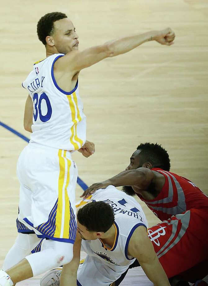 The Warriors' Stephen Curry, left, and Klay Thompson put James Harden in a bind in the final seconds, with the Rockets failing to get off a last shot while trailing by one point. That left Curry celebrating, below left, and the Rockets' Trevor Ariza consoling Harden, below right. Photo: Karen Warren, Staff / © 2015 Houston Chronicle