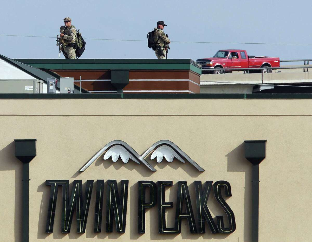 Law enforcement officers stand on top of a Twin Peaks restaurant Tuesday, May, 19, 2015, in Waco, Texas. A deadly weekend shootout involving rival motorcycle gangs at the restaurant apparently began with a parking dispute and someone running over a gang member's foot, police said Tuesday. (Jerry Larson/Waco Tribune-Herald via AP)