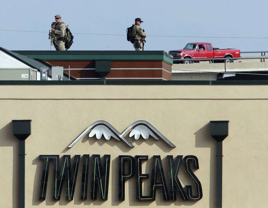 Law enforcement officers stand on top of a Twin Peaks restaurant Tuesday, May, 19, 2015, in Waco, Texas. A deadly weekend shootout involving rival motorcycle gangs at the restaurant apparently began with a parking dispute and someone running over a gang member's foot, police said Tuesday. (Jerry Larson/Waco Tribune-Herald via AP) Photo: Jerry Larson, Associated Press / Waco Tribune-Herald