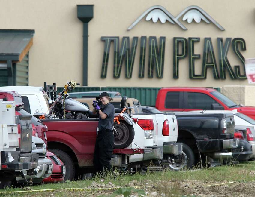 A law enforcement officer photographs a vehicle in the rear parking lot of a Twin Peaks restaurant Tuesday, May, 19, 2015, in Waco, Texas. A deadly weekend shootout involving rival motorcycle gangs apparently began with a parking dispute and someone running over a gang member's foot, police said Tuesday. (Jerry Larson/Waco Tribune-Herald via AP)