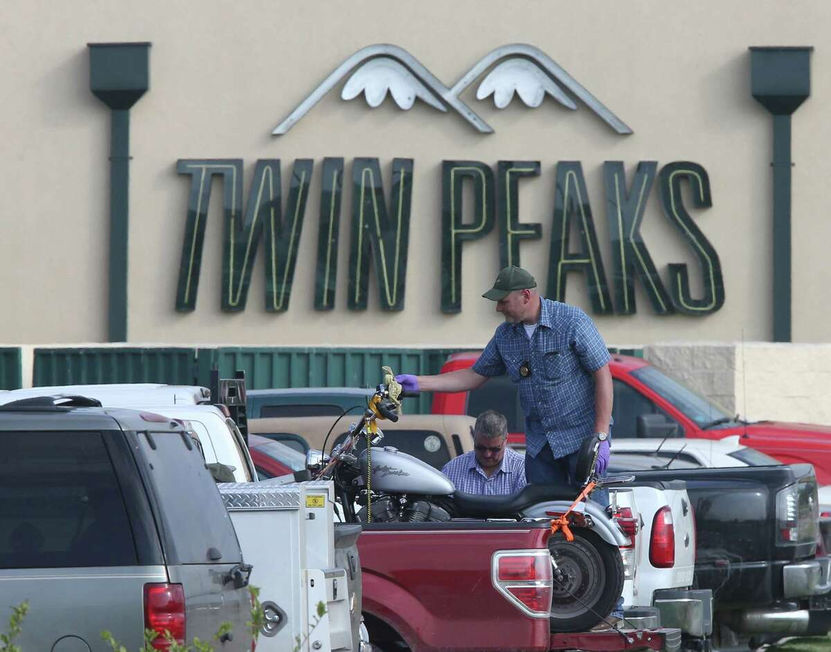 A law enforcement officer examine a motorcycle in a Twin Peaks restaurant parking lot Tuesday, May, 19, 2015, in Waco, Texas. A deadly weekend shootout involving rival motorcycle gangs apparently began with a parking dispute and someone running over a gang member's foot, police said Tuesday. (Jerry Larson/Waco Tribune-Herald via AP)