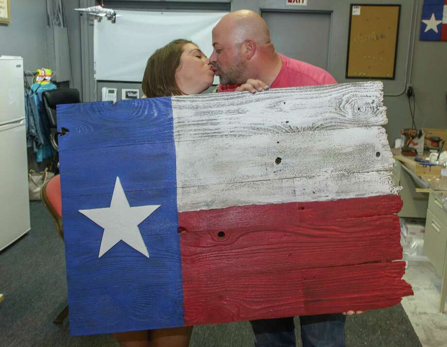 Beth Stratton and Kevin LaGatella share a kiss while displaying the Texas flag they built together during date night at Ballard & Son Construction in Kemah. Their date night included a catered dinner and dessert, and a tool-safety lesson. Photo: ÂKim Christensen, Photographer / ©Kim Christensen