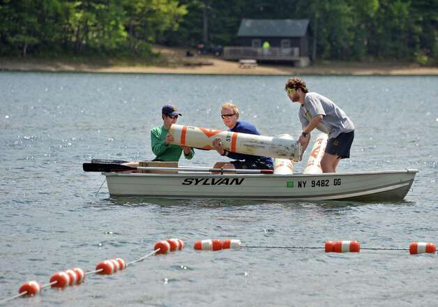 Lifeguards, from left, Ray Hoag, Mac Costello and Sean Kirwan, set up the beach at at Moreau Lake State Park for the holiday weekend Friday May 22, 2015 in Gansevoort, NY.  (John Carl D'Annibale / Times Union) Photo: John Carl D'Annibale / 00031933A