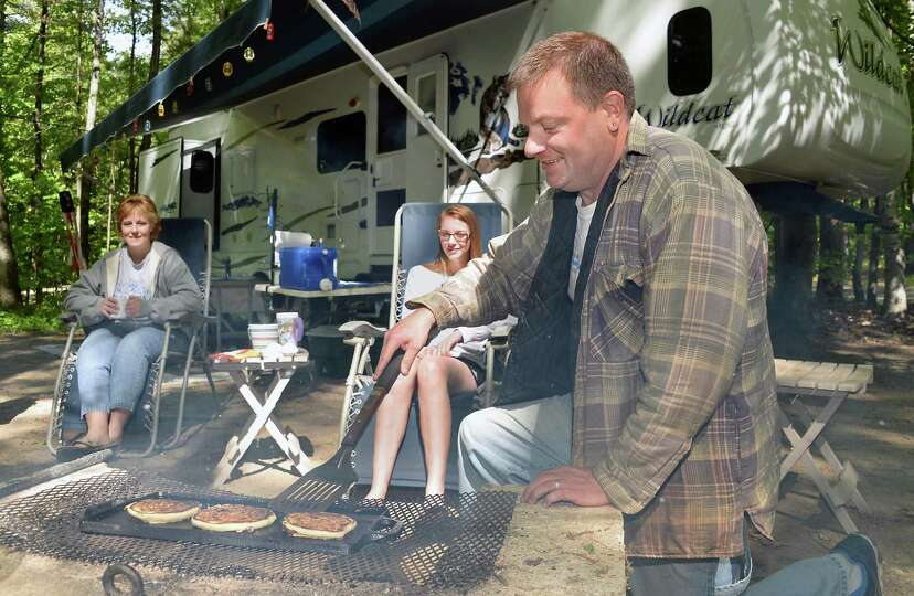 Michael Schultz, right, of Newport, NY, cooks chocolate chip pancakes over a campfire at Moreau Lake