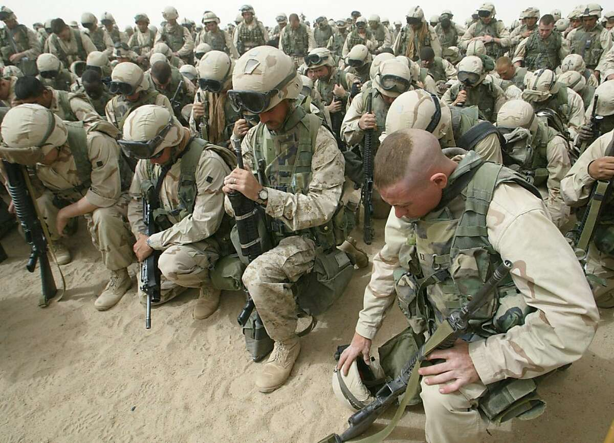 Marines kneel and pray as the 2nd Battalion, 8th Regiment prepares to leave Camp Shoup, north of Kuwait City, in a north-bound direction 20 March, 2003. More than 150,000 allied troops gathered in positions near the Iraqi border to start their advance into southern Iraq. On March 20, 2003 the United States headed a coalition with UK and other forces to invade Iraq.