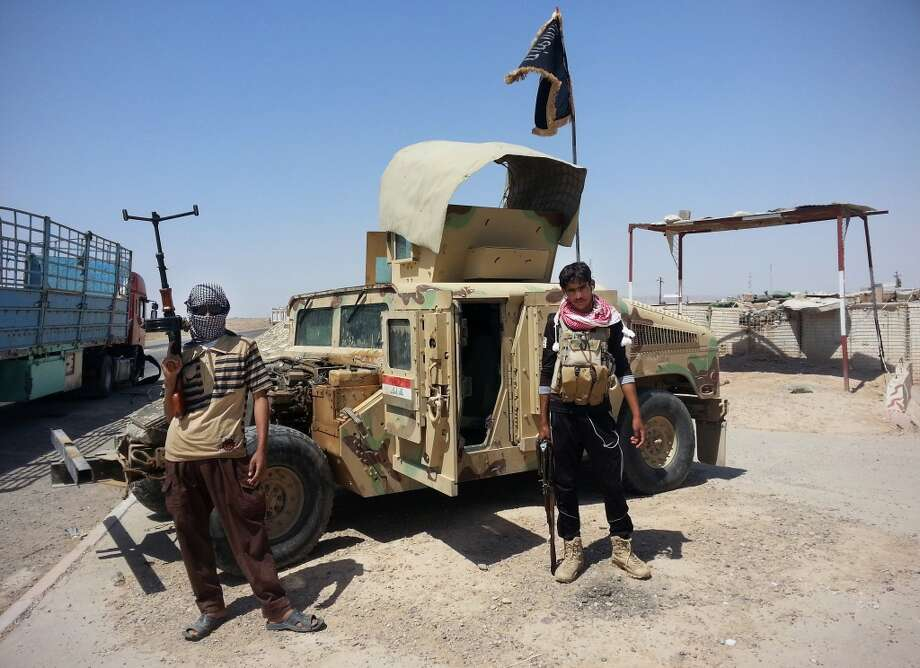 FILE - In this file photo taken Thursday, June 19, 2014, al-Qaeda-inspired militants stand with captured Iraqi army Humvee at a checkpoint outside an oil refinery in Beiji, some 250 kilometers (155 miles) north of Baghdad, Iraq. The government forces on Friday, Nov. 14, drove Islamic State militants out from their remaining strongholds inside the oil refinery town of Beiji, two security official said, in a key victory over the terror group that has captured much of northern and western Iraq in a stunning summer offensive. (AP Photo, File) Photo: Associated Press