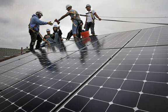 Frank Ross with Grid Alternatives, (left) works with youth from The Rising Sun Energy Center job training program as they install solar panels on the roof of a home in Richmond, Calif., as seen on Fri. May, 22, 2015.