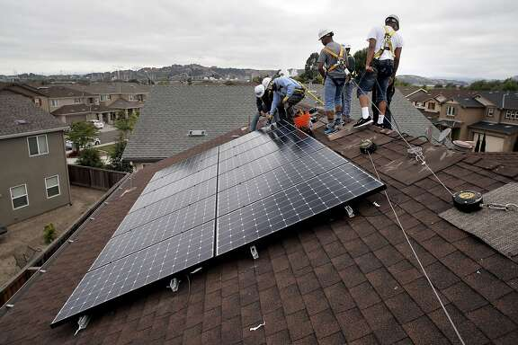 Frank Ross with Grid Alternatives, (second from left) works with youth from The Rising Sun Energy Center job training program as they install solar panels on the roof of a home in Richmond, Calif., as seen on Fri. May, 22, 2015.