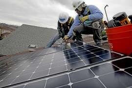 Jose Velasquez, (left) with the Rising Sun Energy Center job training programis instructed by roof supervisor, Frank Ross with Grid Alternatives, as they install solar panels on the roof of a home in Richmond, Calif., as seen on Fri. May, 22, 2015.