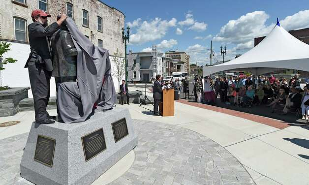 Brian Merriam, who oversaw the fundraising for the monument to the two pillars of electricity, replaces the shroud that was blown from the statues by high winds prematurely unveiled the bronzes of Thomas Edison and Charles Steinmetz at their official unveiling at the corner of Erie Blvd. and Ferry Street Friday, May 22, 2015, in Schenectady, N.Y. (Skip Dickstein/Times Union) Photo: SKIP DICKSTEIN / 00031947A
