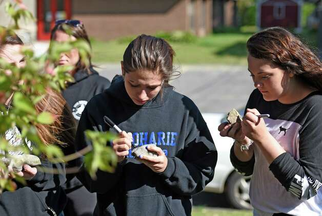 Winter Speracin, left and Alexis Borst of the Schoharie High School Volleyball team inscribe personal messages on rocks that were placed at the base of a flowering dogwood tree that they planted on the grounds of Mekeel Christian Academy Friday morning May 22, 2015, in memory of Mekeel Volleyball captain Carly Sinnott in Scotia, N.Y.    (Skip Dickstein/Times Union) Photo: SKIP DICKSTEIN / 00031966A