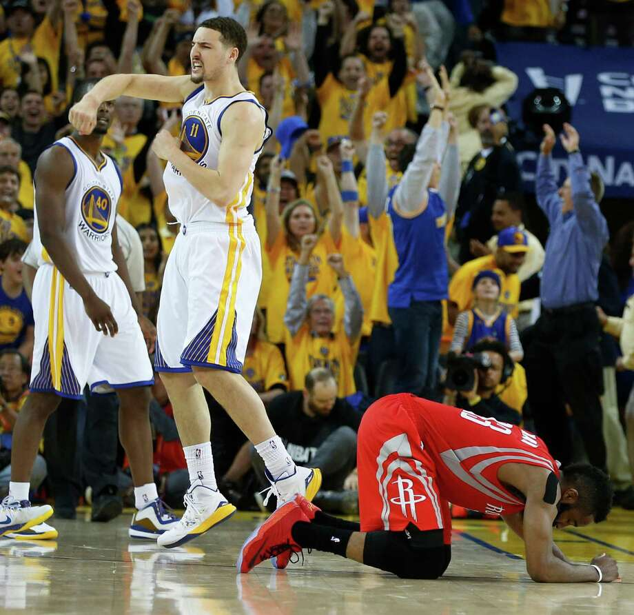 Rockets guard James Harden goes to the floor as Warriors guard Klay Thompsoncelebrate Golden State's 99-98 win in Game 2 of the NBA Western Conference finals at Oracle Arena. Photo: James Nielsen, Staff / © 2015  Houston Chronicle