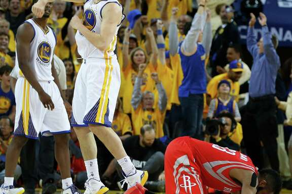 Rockets guard James Harden goes to the floor as Warriors guard Klay Thompsoncelebrate Golden State's 99-98 win in Game 2 of the NBA Western Conference finals at Oracle Arena.