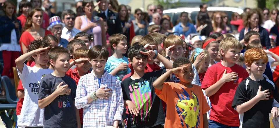 Veterans Park Elementary School students salute the flag during the annual Memorial Day program at t