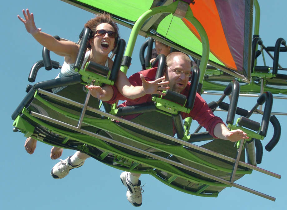 "Ellie Grosso of Trumbull, left, and friend Bob Sembiante ride the ""Cliff Hanger"" during the Trumbull Day festivities at Hillcrest Middle School in 2007. Trumbull Day has been cancelled in past years due to its expense and plans for this year are still up in the air. Photo: File Photo / Connecticut Post File Photo"
