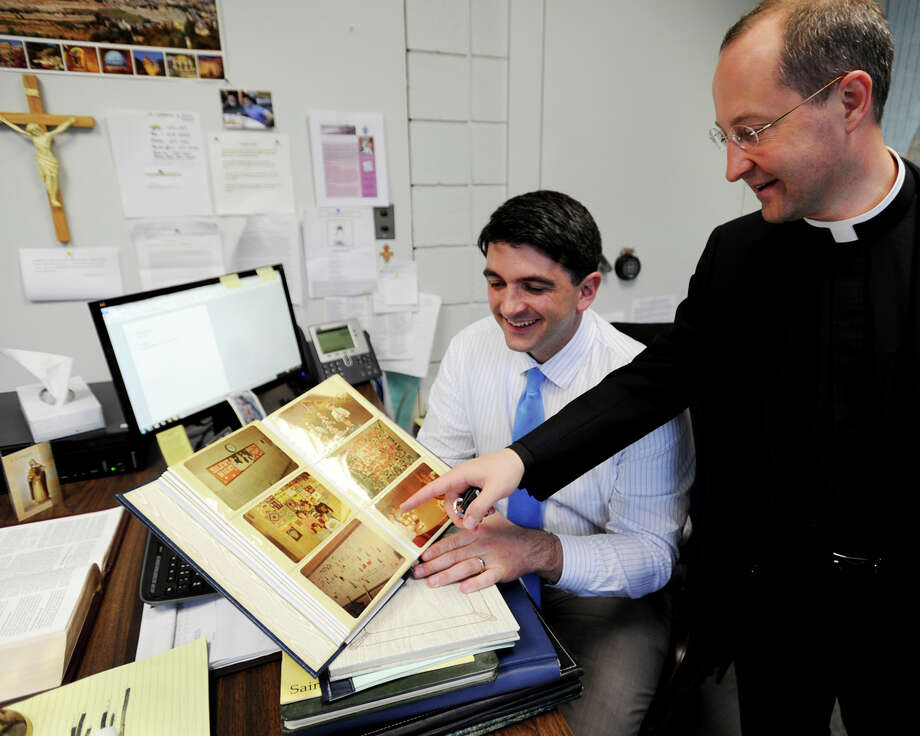 Principal Peter Rodgers and Father Joseph Marcello looks over a scrapbook of old school photos at St. Catherine of Sienna School, celebrating its 50th anniversary in Trumbull, Conn. on Tuesday, May 19, 2015. Photo: Brian A. Pounds / Connecticut Post