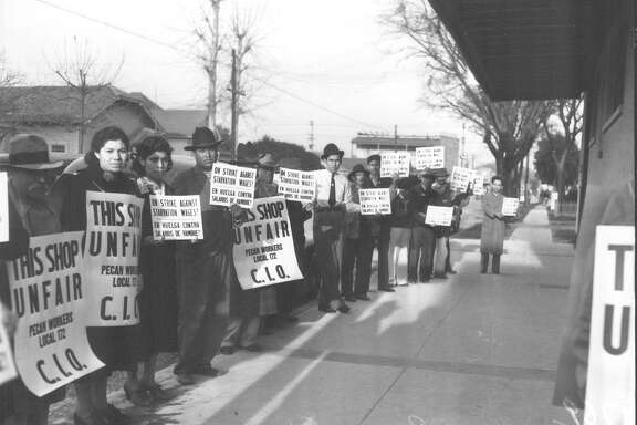 Striking pecan shellers picketing on the sidewalk in front of Southern Pecan Shelling Company at 135 E. Cevallos Street. Photo published in the Light on Feb. 25, 1938.