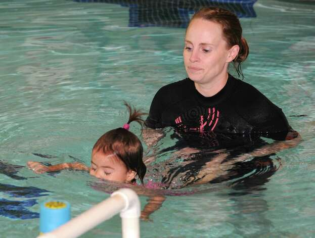 """Anthea Morris teaches Sophia Alvear Miranda, 1 1/2 yrs-old, of Duanesburg how to swim at Mohonasen High School Wednesday, May 13, 2015 in Schenectady, N.Y. This swim instruction program teaches children as young as 6 months to keep their head above water and, in some cases, """"swim"""" to the edge of the pool. (Lori Van Buren / Times Union) Photo: Lori Van Buren / 00031815A"""