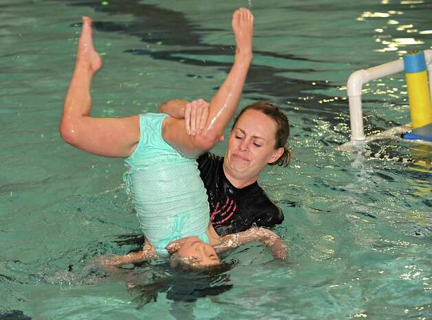 "Anthea Morris flips Eva Dunham, 3 of Glenville during a swimming lesson at Mohonasen High School Wednesday, May 13, 2015 in Schenectady, N.Y. This swim instruction program teaches children as young as 6 months to keep their head above water and, in some cases, ""swim"" to the edge of the pool. Eva was almost a drowning victim when she was younger. (Lori Van Buren / Times Union) Photo: Lori Van Buren / 00031815A"