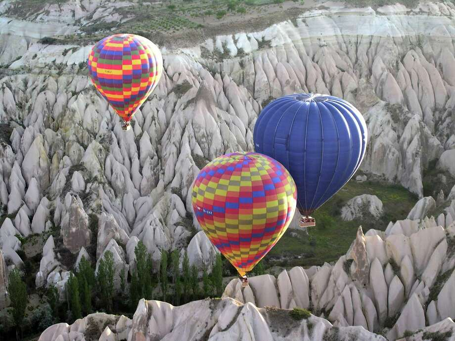 Hot-air balloons rise to the sky at sunrise in Cappadocia, Turkey. The valley is filled with tall, thin spires of stone and ancient settlements cut into rock. Photo: UZAY HACAOGLU, STR, STR / AP