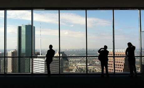 People look out the windows of the JPMorgan Chase Tower's 60th floor observation deck.