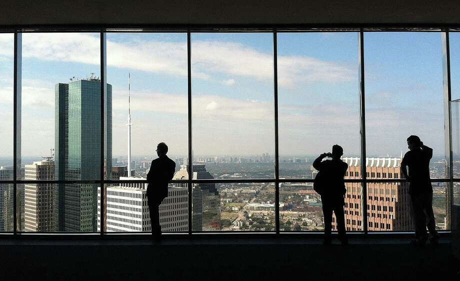 People look out the windows of the JPMorgan Chase Tower's 60th floor observation deck. Photo: James Nielsen, Staff / © Houston Chronicle 2013
