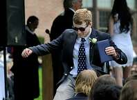 Bryce Giopal kicks his heels in the air after receiving his diploma from Canterbury School in New Milford, Conn., Friday, May 22, 2015, at graduation exercises.