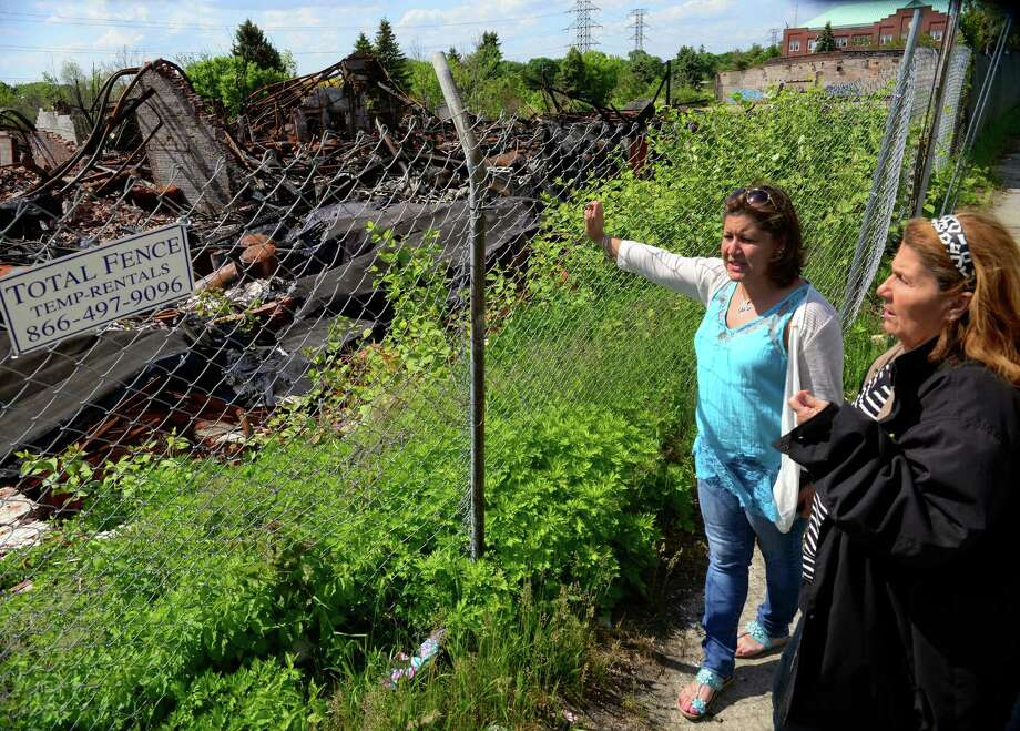 Bridgeport City Councilwomen Lydia Martinez, right, and Milta Feliciano at the site of the destroyed Rowayton Trading Company along Seaview Ave in Bridgeport, Conn., on Friday May 22, 2015. The block long structure was destroyed by fire in 2014 and it has yet to be cleaned up. Photo: Christian Abraham / Connecticut Post