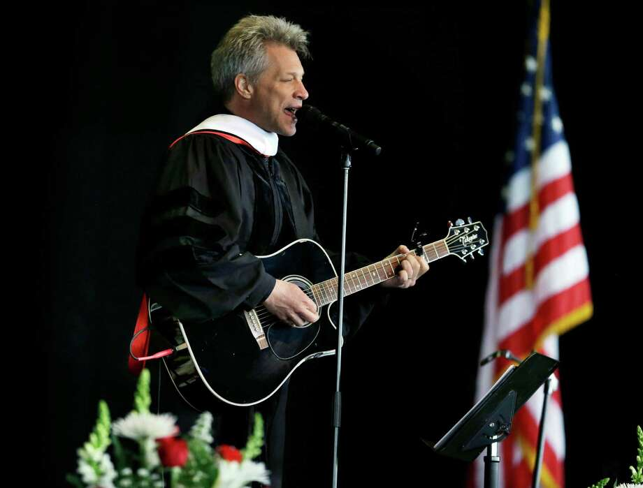 """Rock star and philanthropist Jon Bon Jovi performs a new song during graduation ceremonies at Rutgers University-Camden Thursday, May 21, 2015, in Camden, N.J. The New Jersey native premiered a new song, """"Reunion,"""" which he said was a gift to the graduates. It began, """"This isn't how the story ends, my friends, it's just a fork along the road."""" Bon Jovi and Bryan Stevenson, public interest lawyer and founder and executive director of the Equal Justice Initiative, received honorary degrees. (AP Photo/Mel Evans) Photo: Mel Evans, STF / AP"""